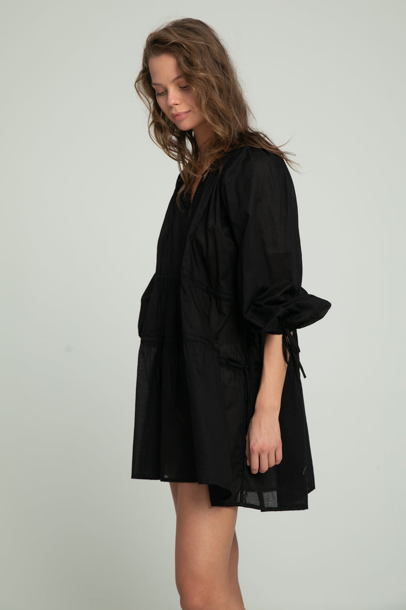 A woman wearing a black cotton dress for summer by Lilya