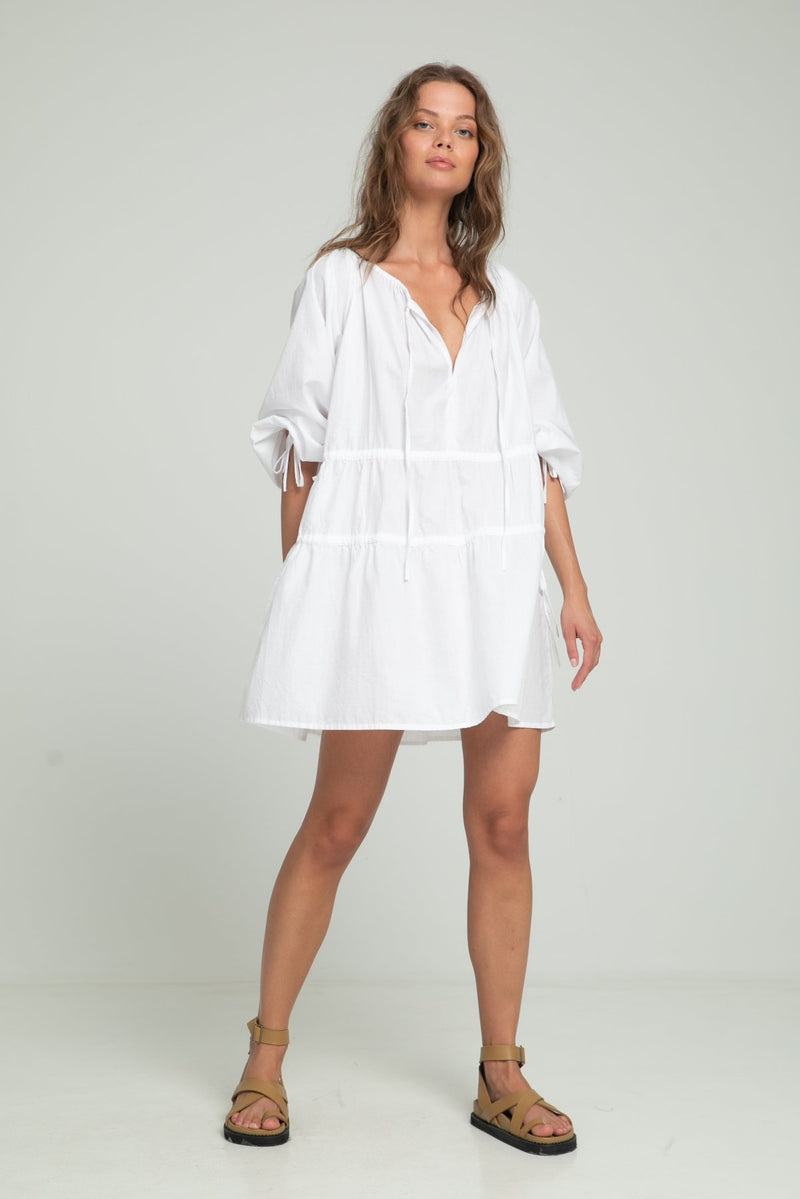 A woman wearing a relaxed fitting white cotton dress by Lilya