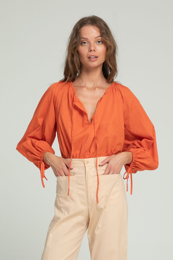 A woman in a tangerine boho cotton top by Lilya