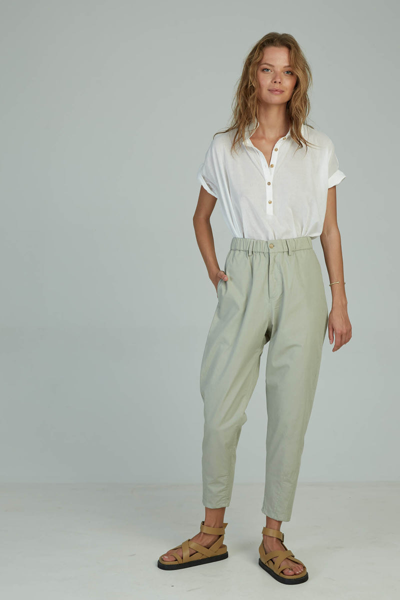 A woman in a high waist cotton pant for summer by Lilya