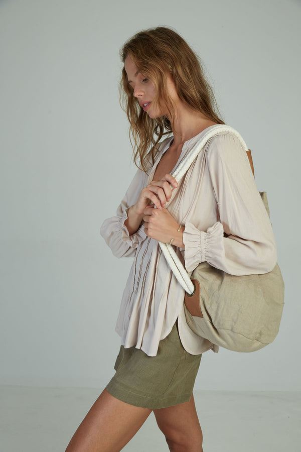 A woman with a neutral colour linen bag by Lilya