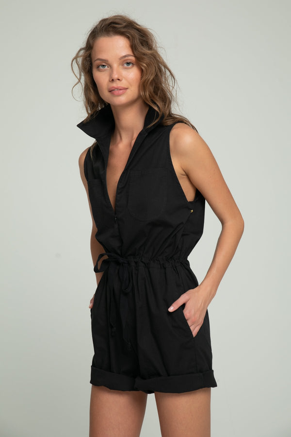 A woman wearing a short black summer playsuit by Lilya
