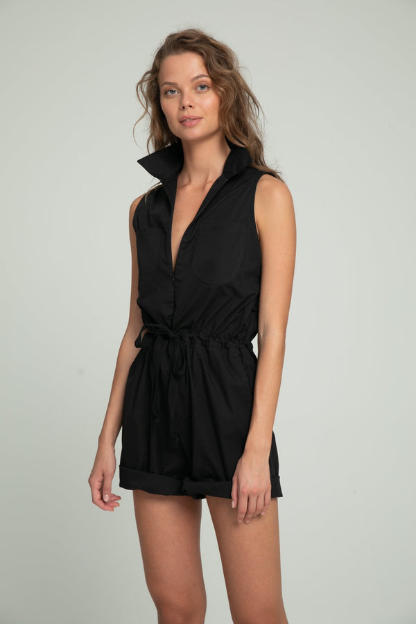 A woman wearing a black cotton playsuit by Lilya