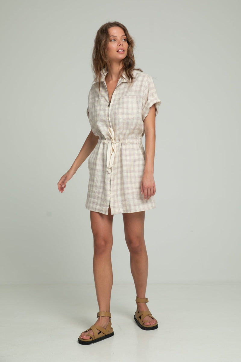 A woman in a mini linen dress in check pattern by Lilya