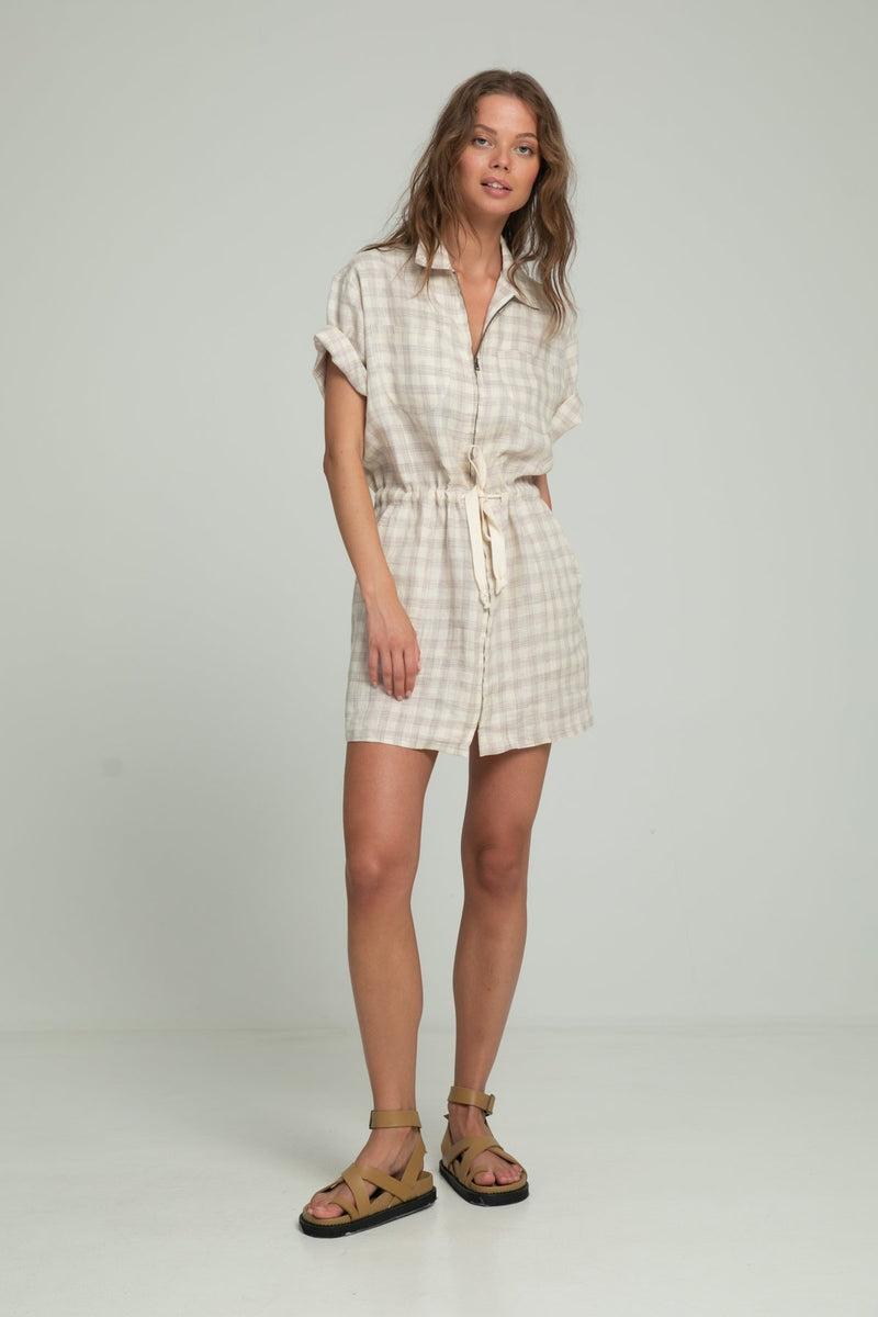 A woman wearing a linen dress for summer in check pattern by Lilya