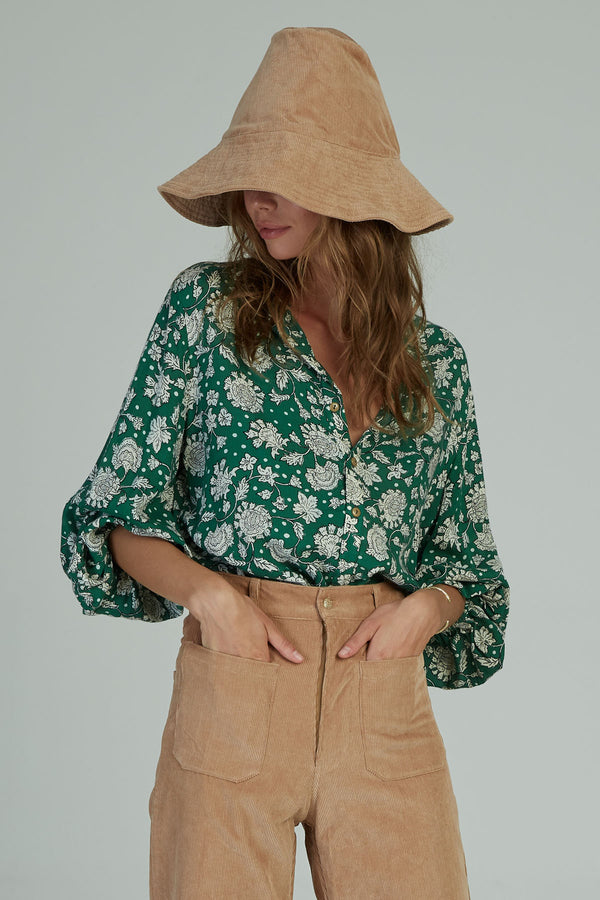 A woman in a green floral Agatha Top by Lilya