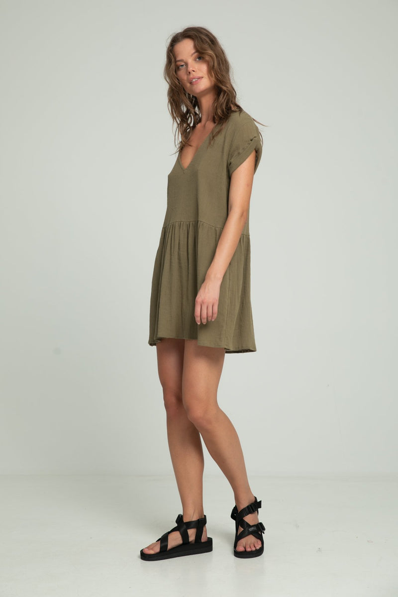 A woman in a short sleeve khaki dress by Lilya