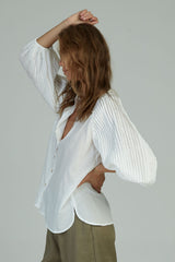 A woman in a romantic pintucked cotton top by Lilya