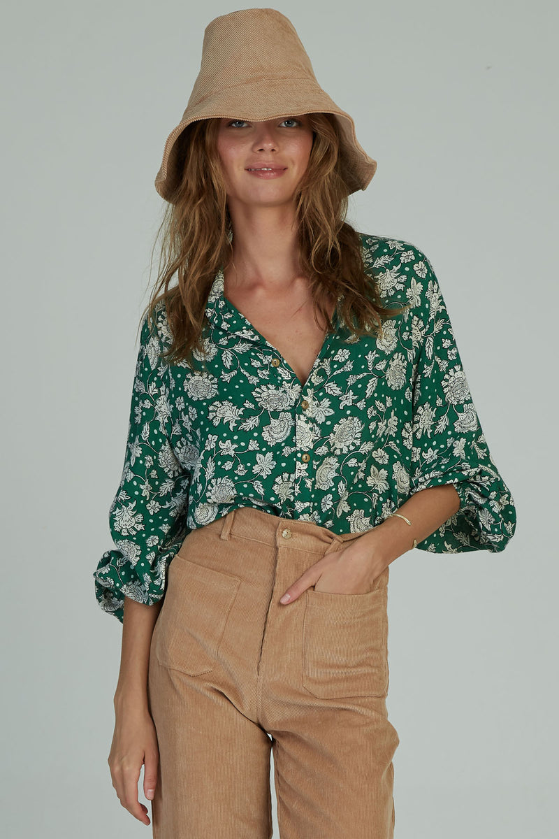 A woman in a floral Agatha Top by Lilya for Autumn