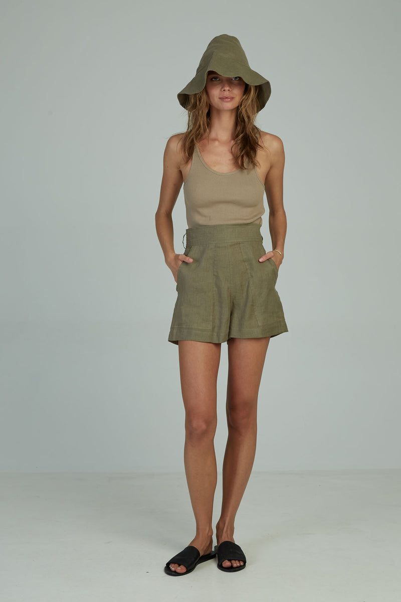A woman wearing linen high wasited shorts by Lilya