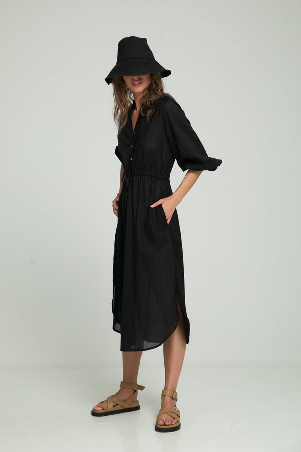 A woman wearing a Lilya black summer dress