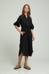 A woman wearing a black dress with pockets by Lilya for summer