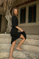 A woman wearing a black midi summer dress by Lilya