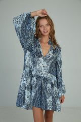 A woman in a paisley blue mini dress by Lilya
