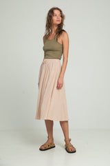 A woman in a khaki singlet from cotton and a light beige skirt by Lilya