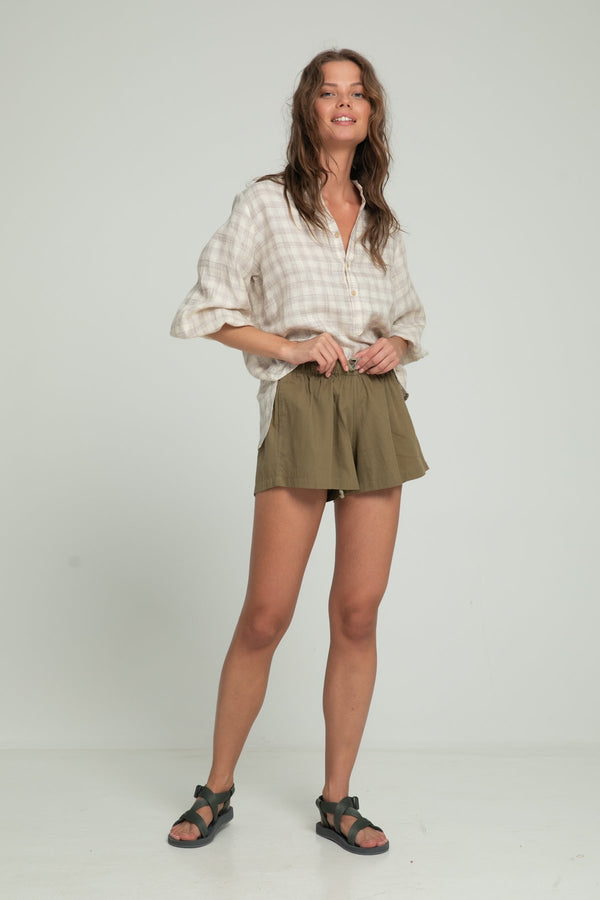 A woman wearing khaki cotton shorts and a check blouse by Lilya