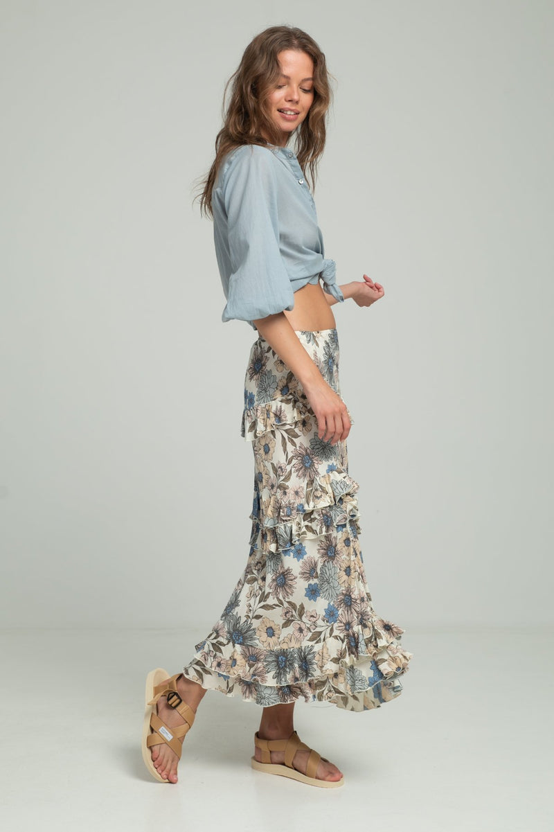 A woman wearing floral maxi skirt and a blue blouse by Lilya