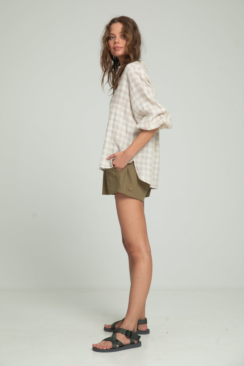 A woman in a linen summer blouse and cotton shorts by Lilya