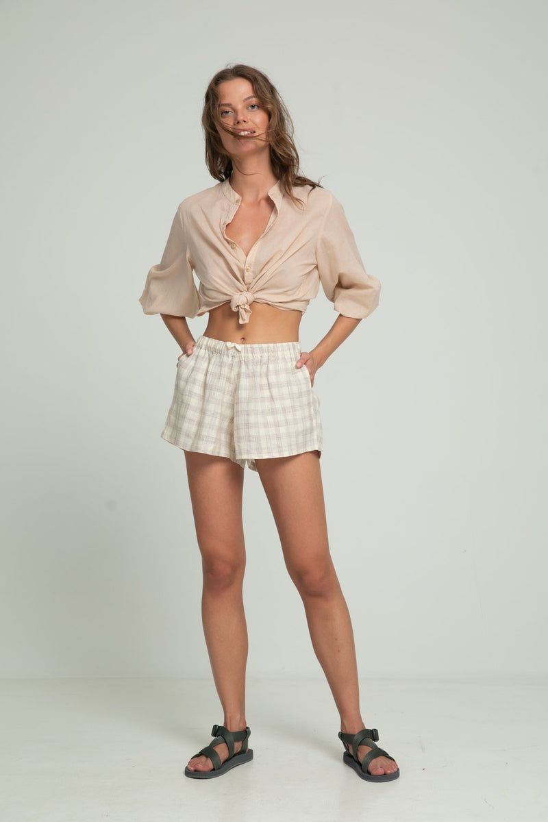 A woman in summer linen shorts and a beige blouse by Lilya