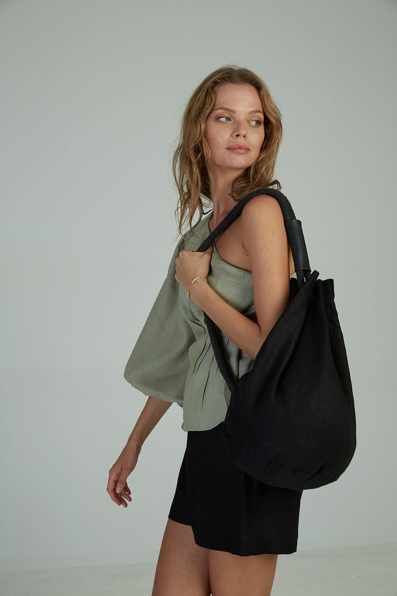 A woman carrying a black linen casual bag by Lilya