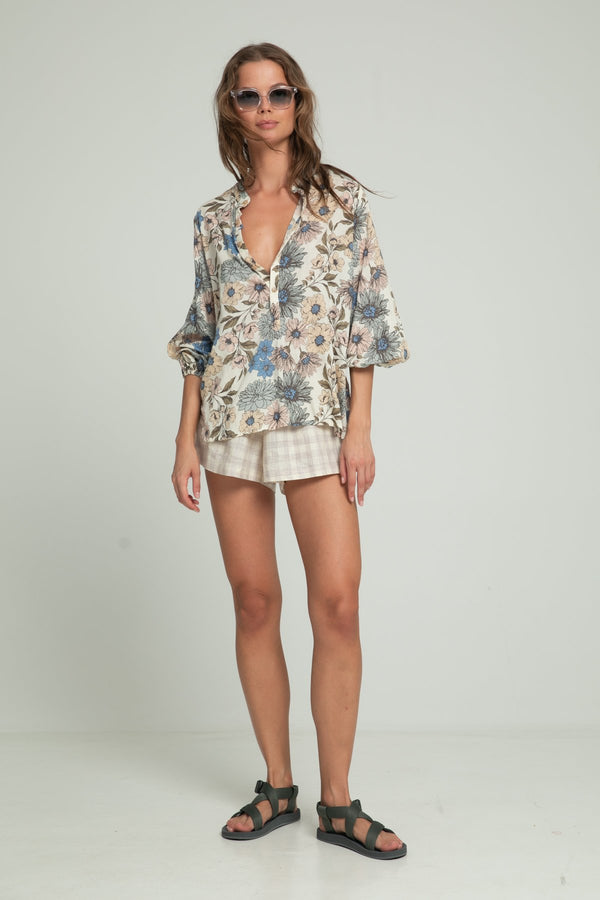 A woman wearing linen shorts in check pattern and a floral blouse by Lilya