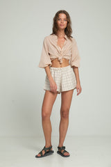 A woman in a buttoned beige blouse and check linen shorts by Lilya