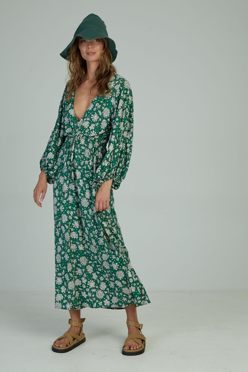 A woman in a floral maxi wrap dress by Lilya