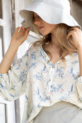 A woman in a summer long sleeve floral top by Lilya