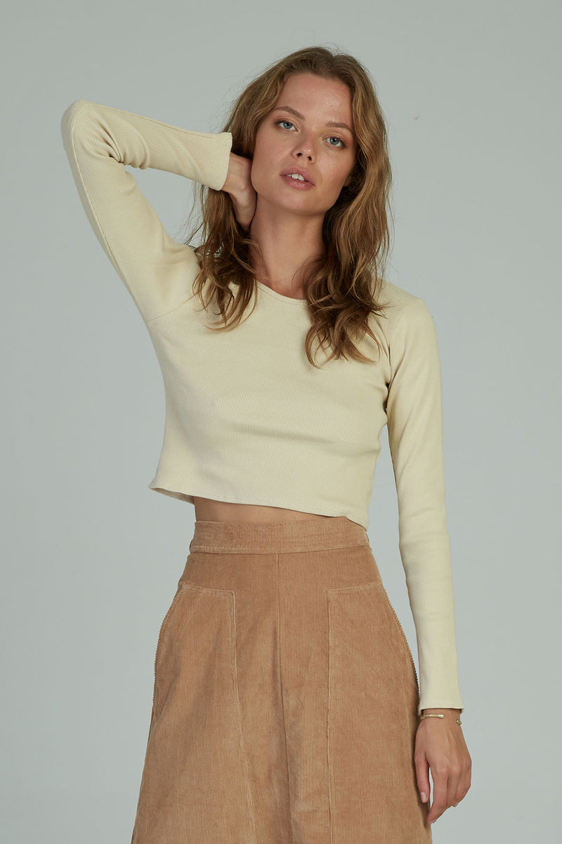 A woman in a long sleeved cropped top by Lilya in Australia