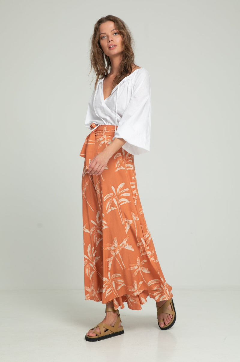 A woman in a tropical print summer wrap skirt by Lilya