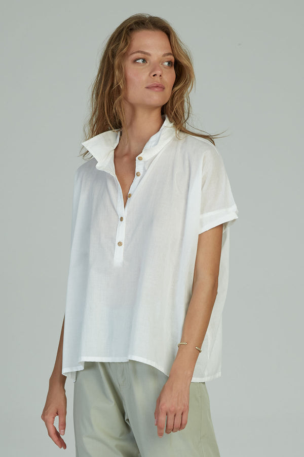 A woman in a classic white short sleeve top for work by Lilya