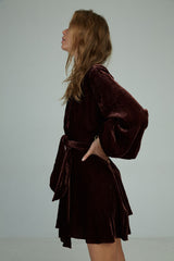 A woman wearing a mini velvet dress for winter with long sleeves by Lilya