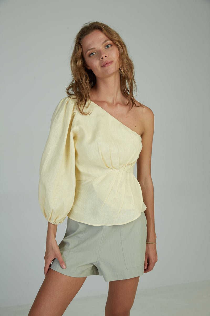 A woman in a linen one shoulder top for summer by Lilya