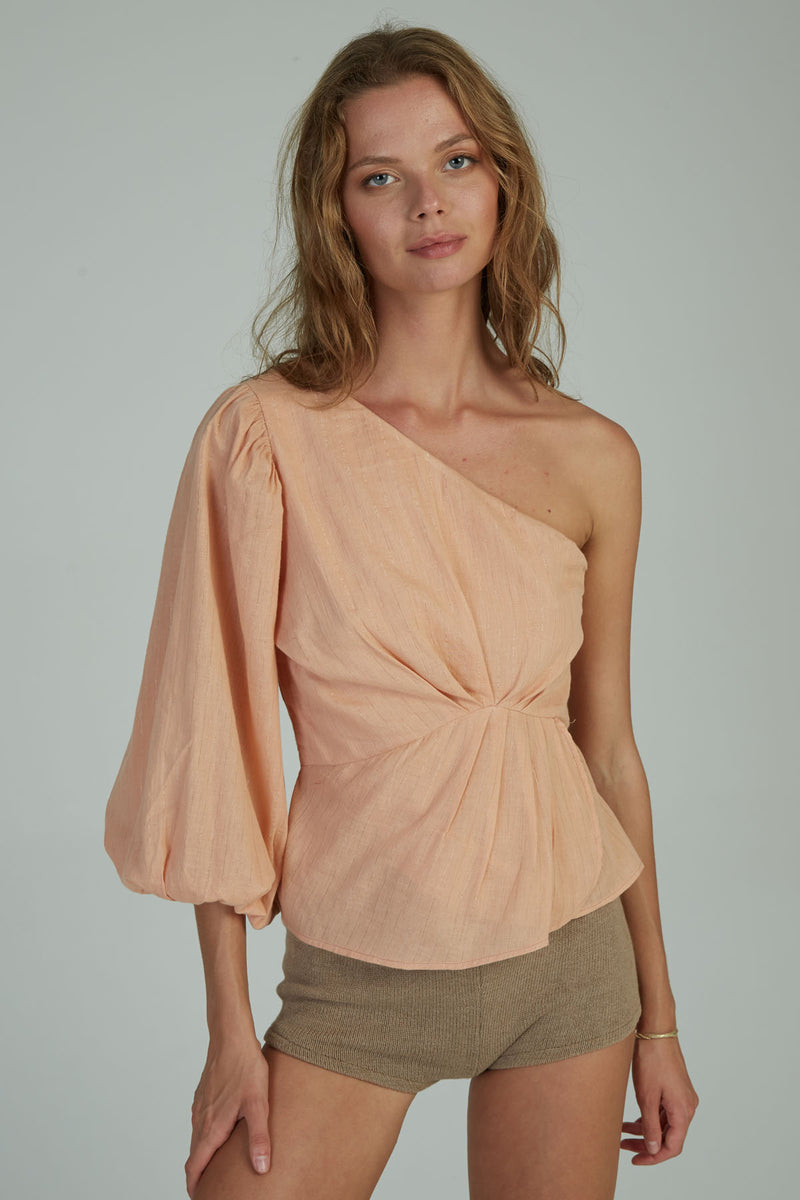 A woman wearing a one shoulder dressy top by Lilya