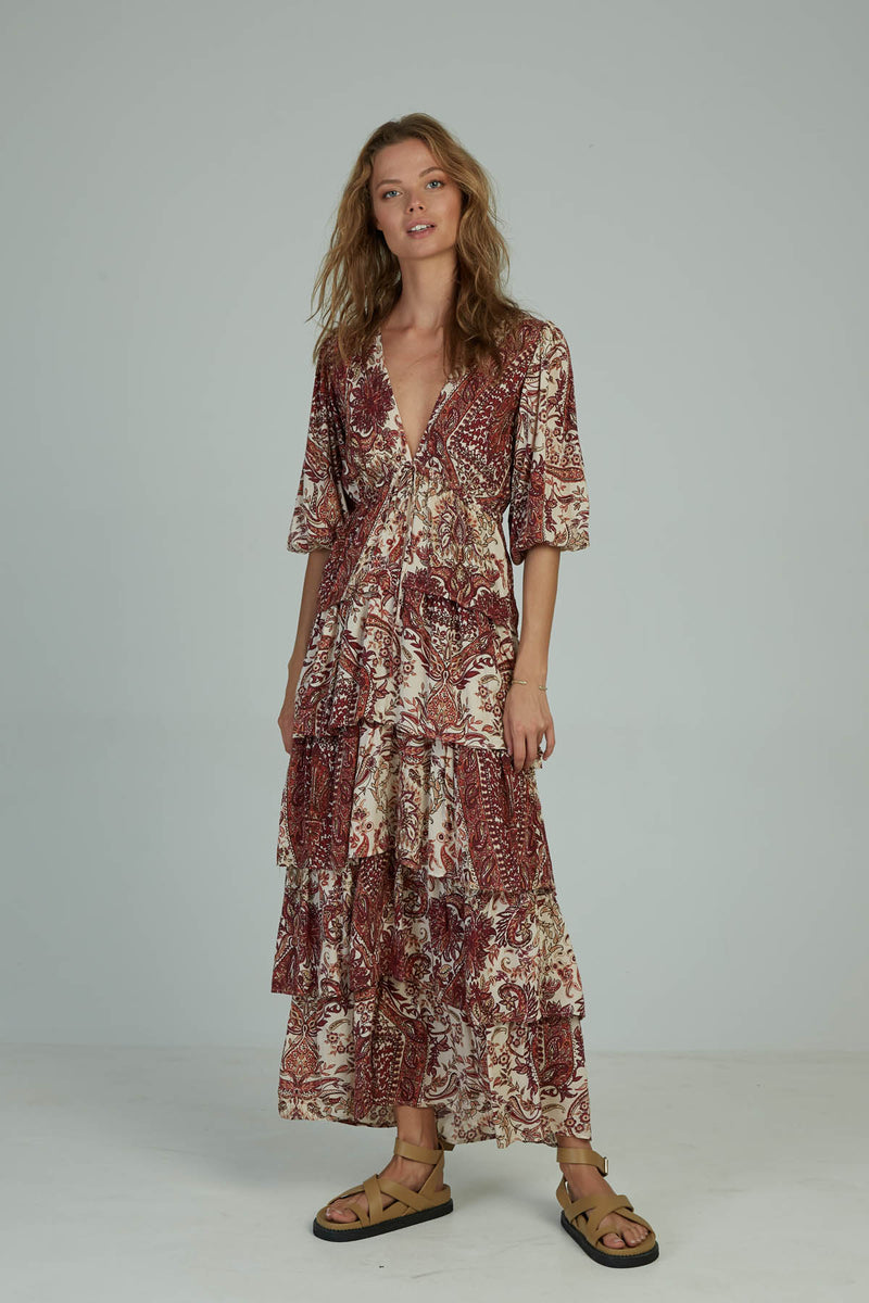 A woman in a paisley maxi frill dress by Lilya in Australia