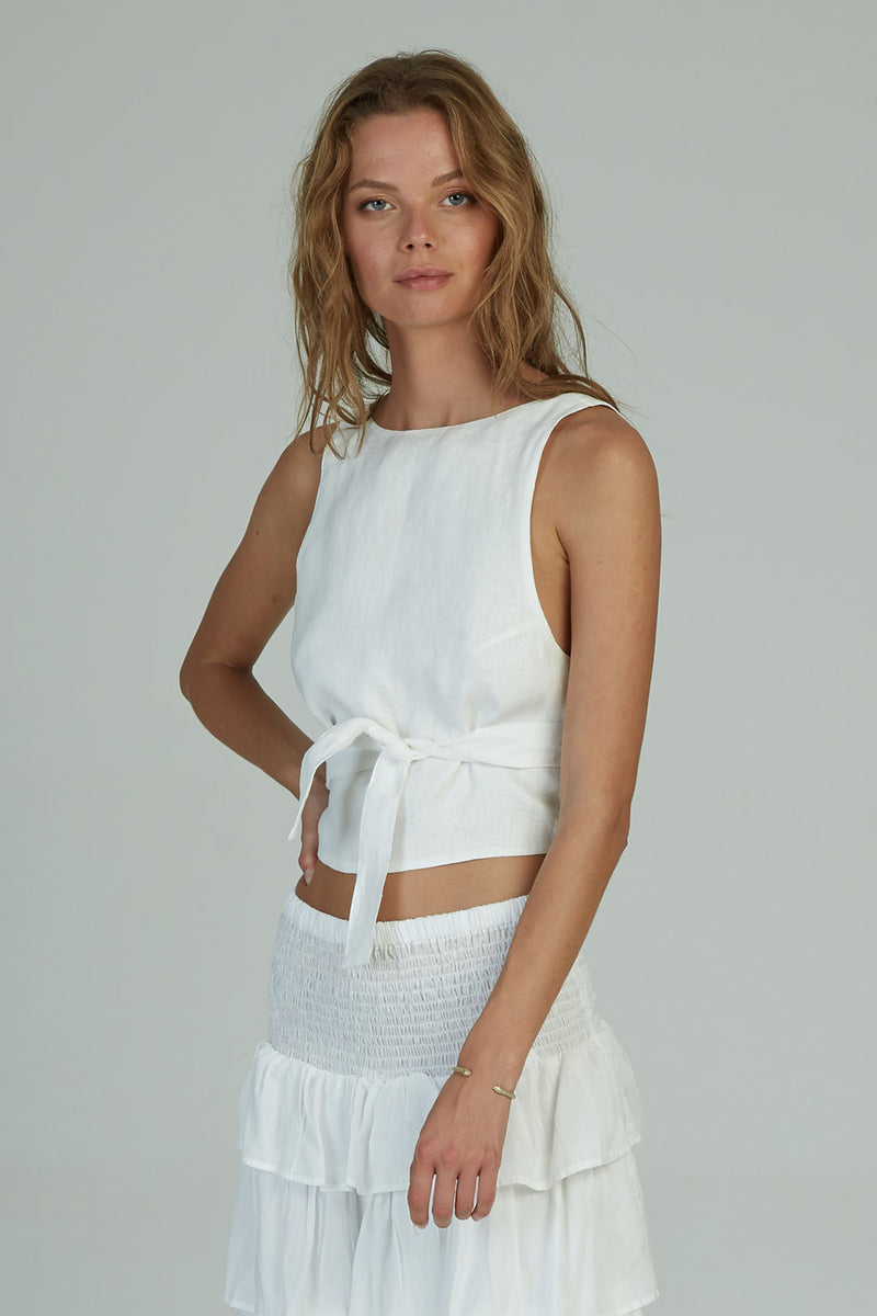 A woman wearing a white linen wrap top for Summer by Lilya