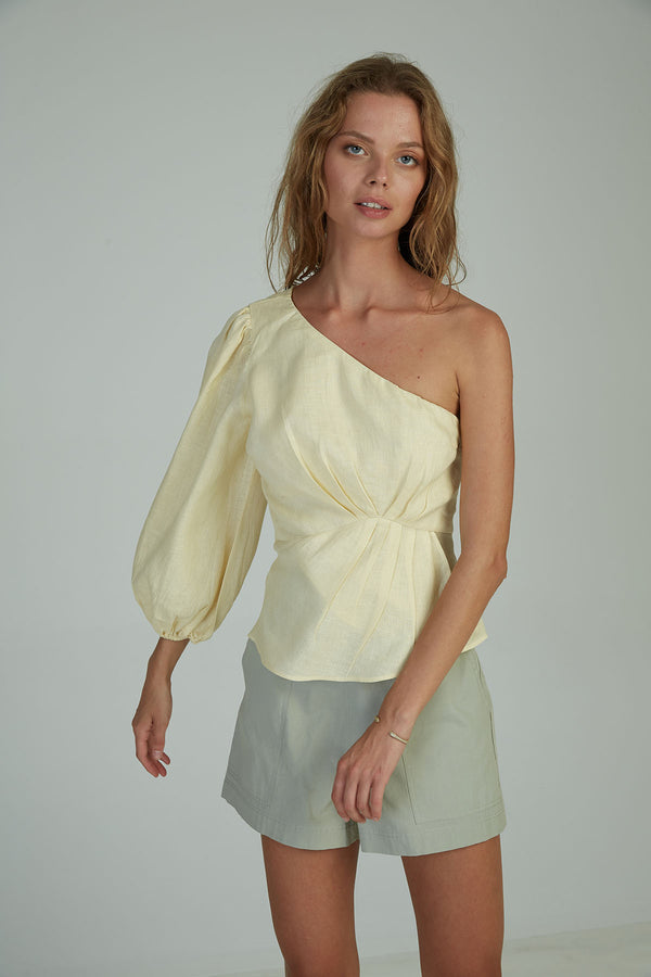 A woman in a feminine on shoulder top made by Lilya in Australia
