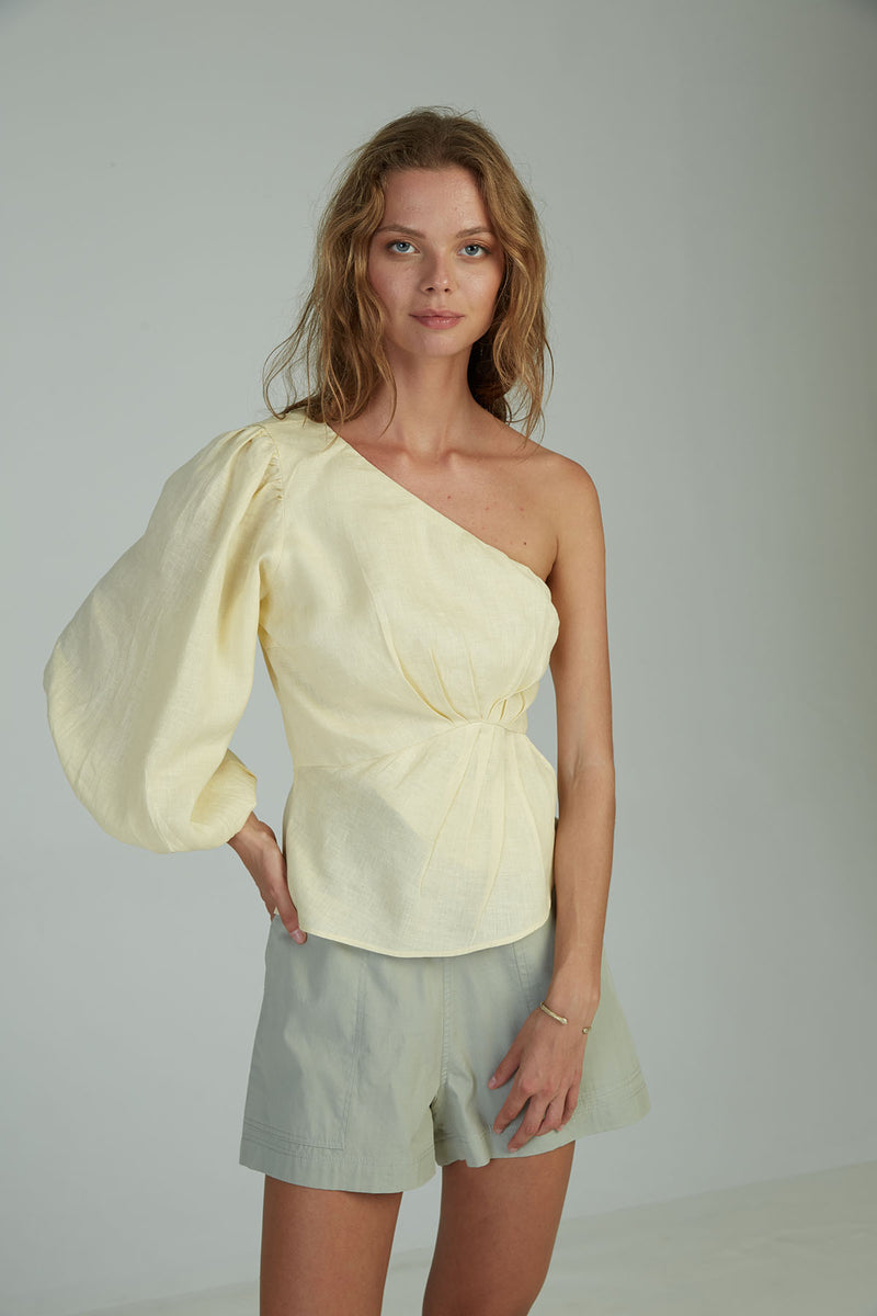 A woman in a classic linen one shoulder top by Lilya