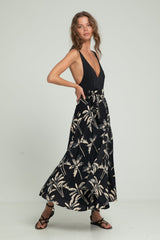 A woman in a black bodysuit with summer wrap skirt by Lilya
