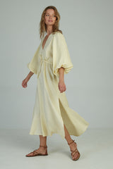 A woman wearing a summer linen maxi dress by Lilya