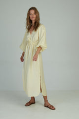 A woman wearing a plain linen maxi dress by Lilya for summer