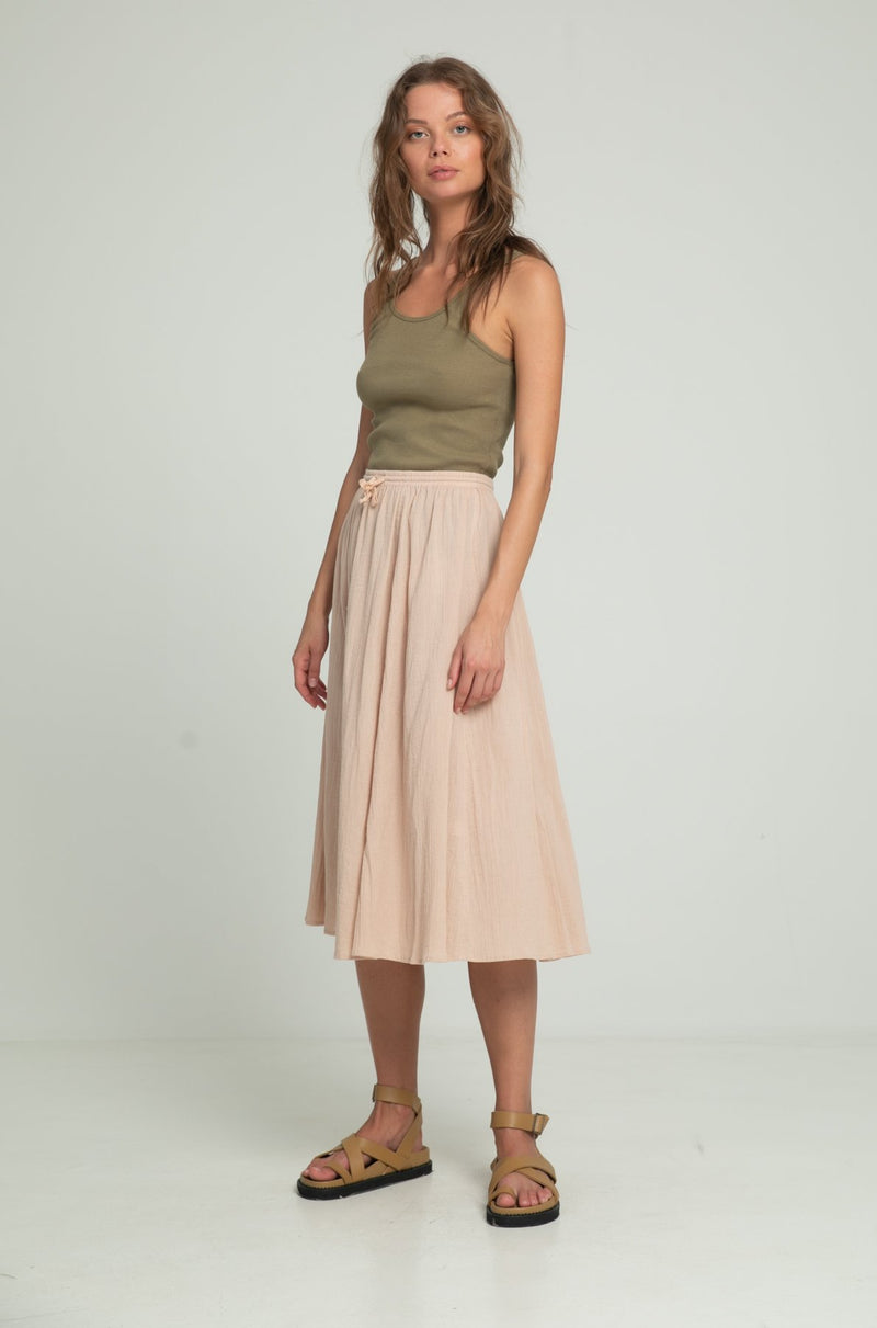 A woman in a midi beige cotton skirt and khaki top by Lilya