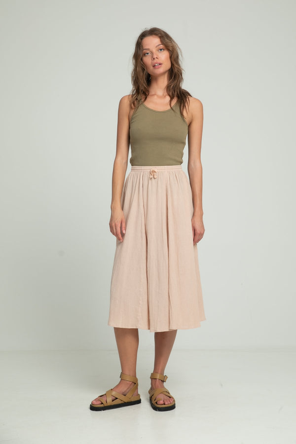 A woman wearing summer cotton skirt and a khaki top by Lilya