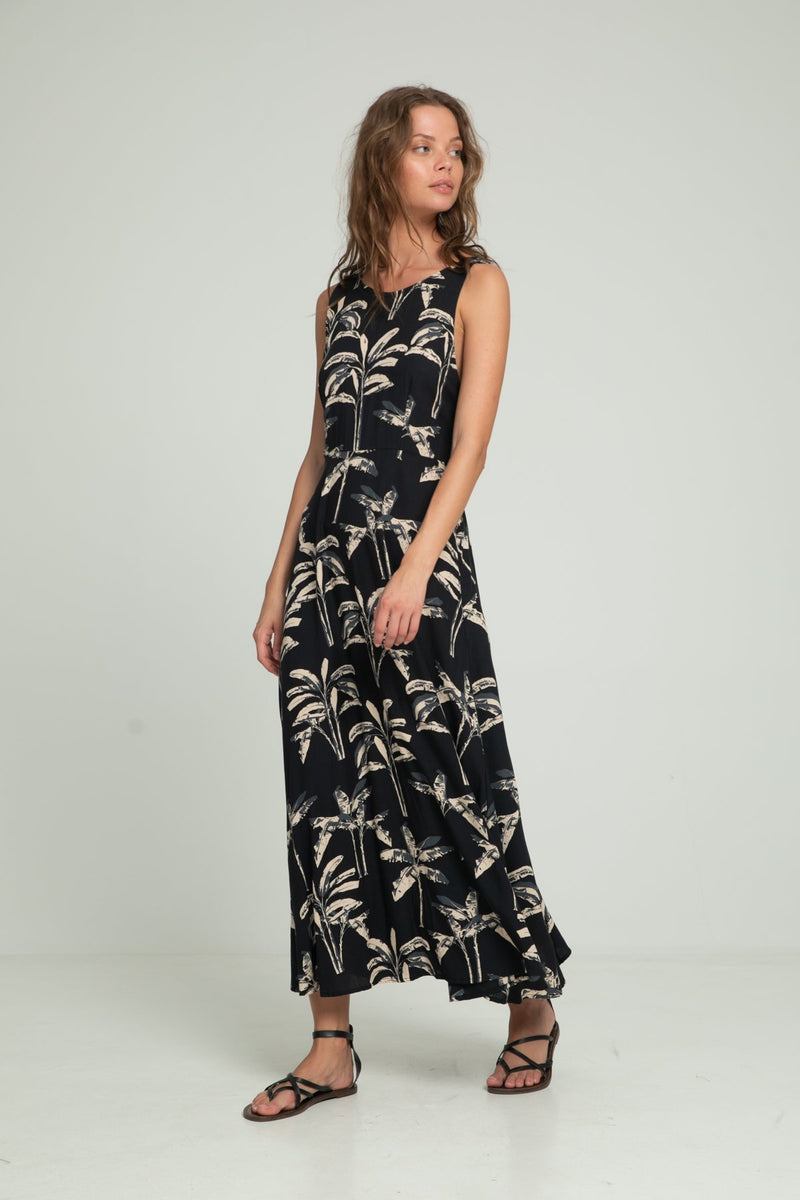 A woman wearing a tropical print summer maxi dress by Lilya