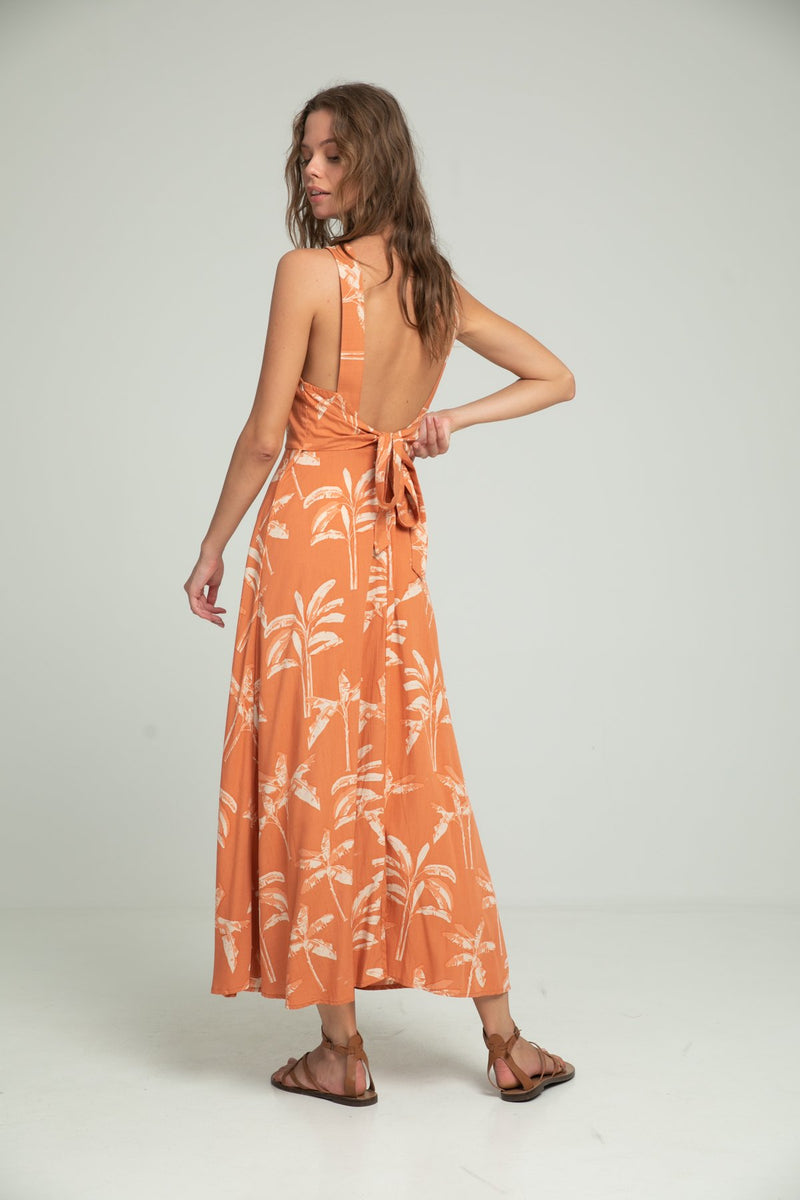 A woman in a tropical print summer maxi dress by Lilya