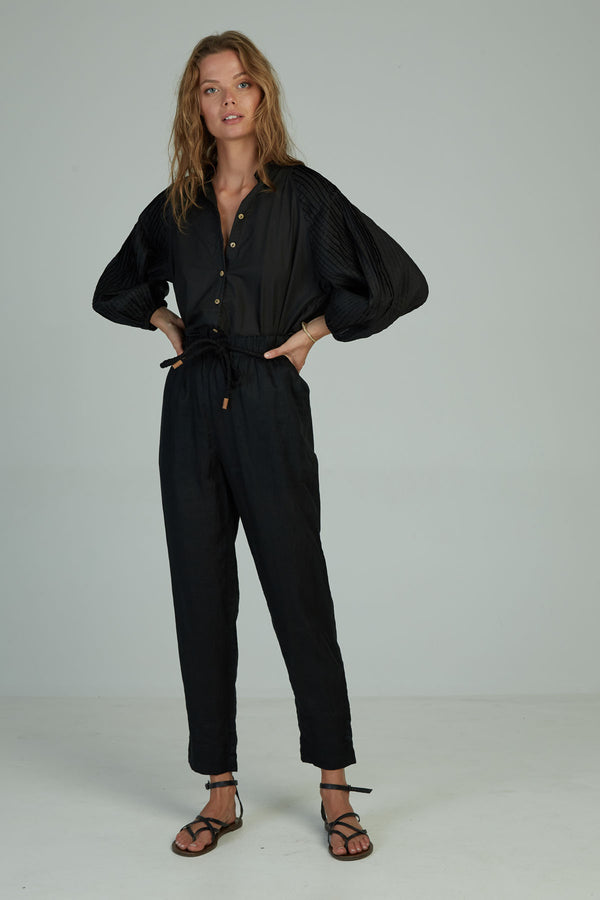 A woman wearing winter black linen pants by Lilya in Australia