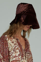 A woman wearing a wine coloured velvet bucket hat for winter by Lilya