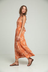 A woman wearing a resort dress with banana leaf print for summer by Lilya
