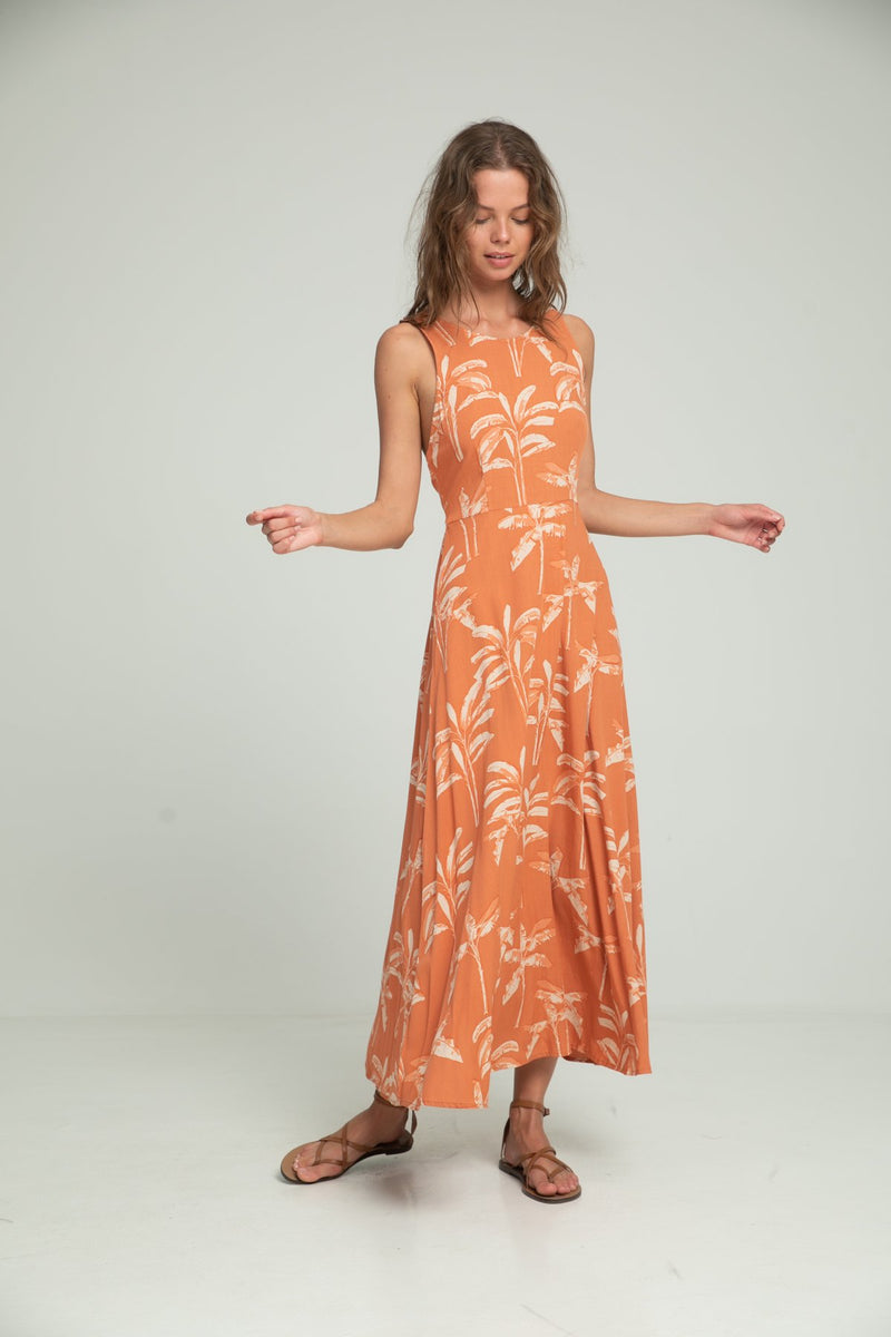 A woman wearing a palm print maxi dress by Lilya