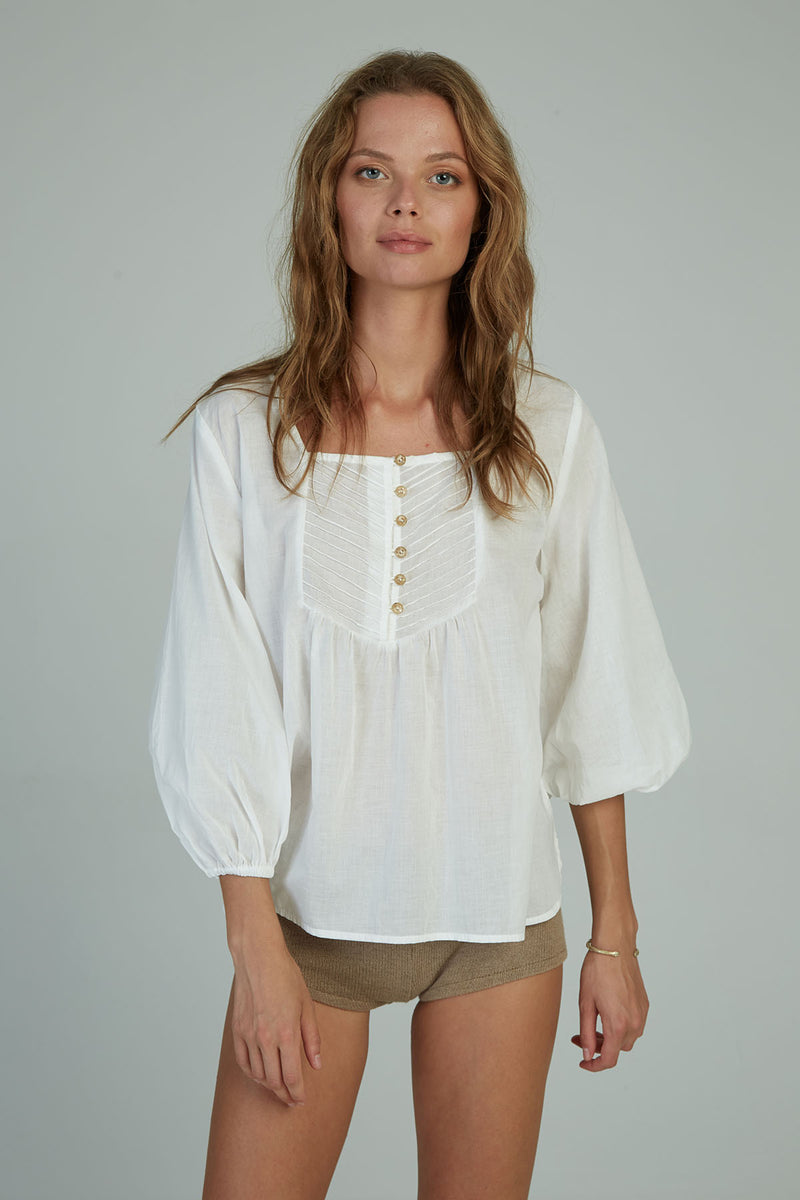 A woman in a romantic white cotton top by Lilya